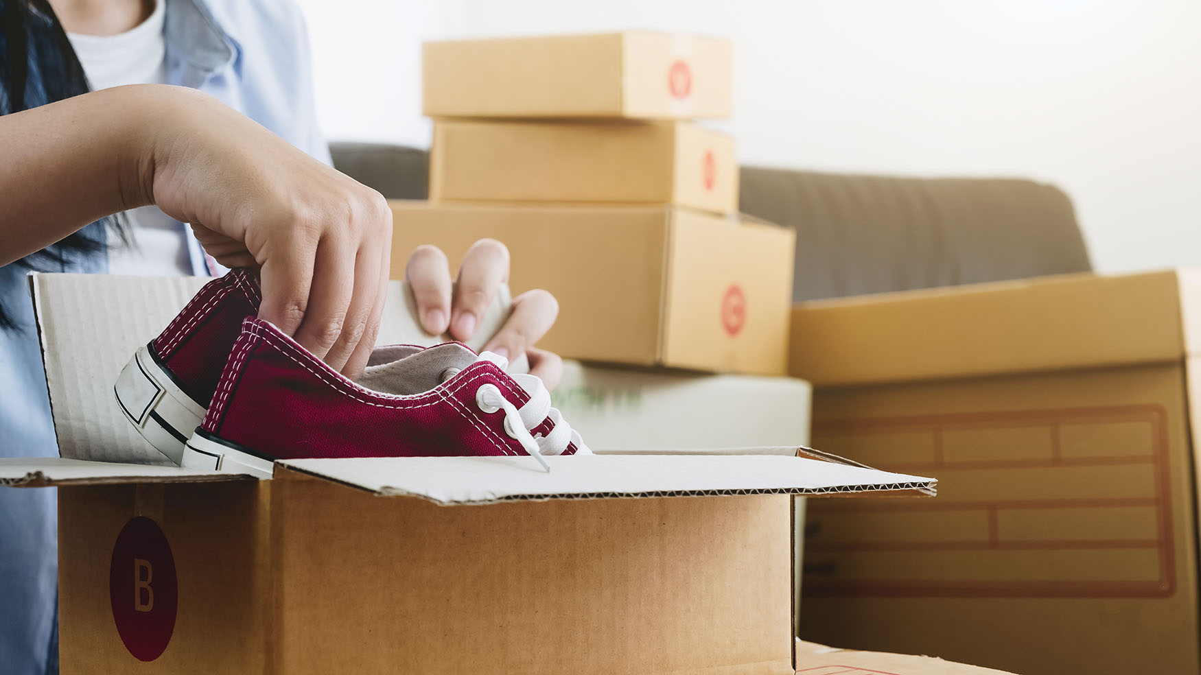 Young woman putting red sneakers in moving box