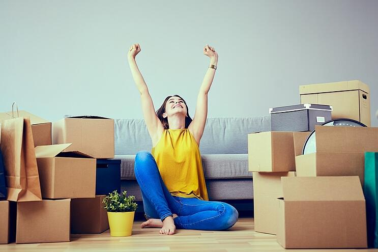 woman in a yellow top surrounded by moving boxes
