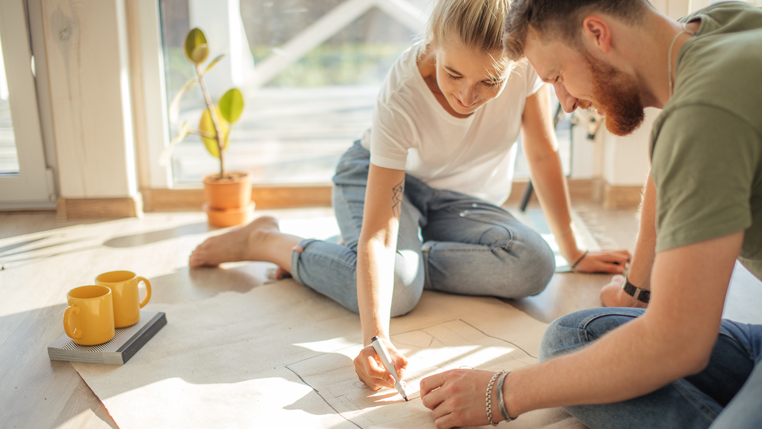 Young couple planning their home move on clean living room floor