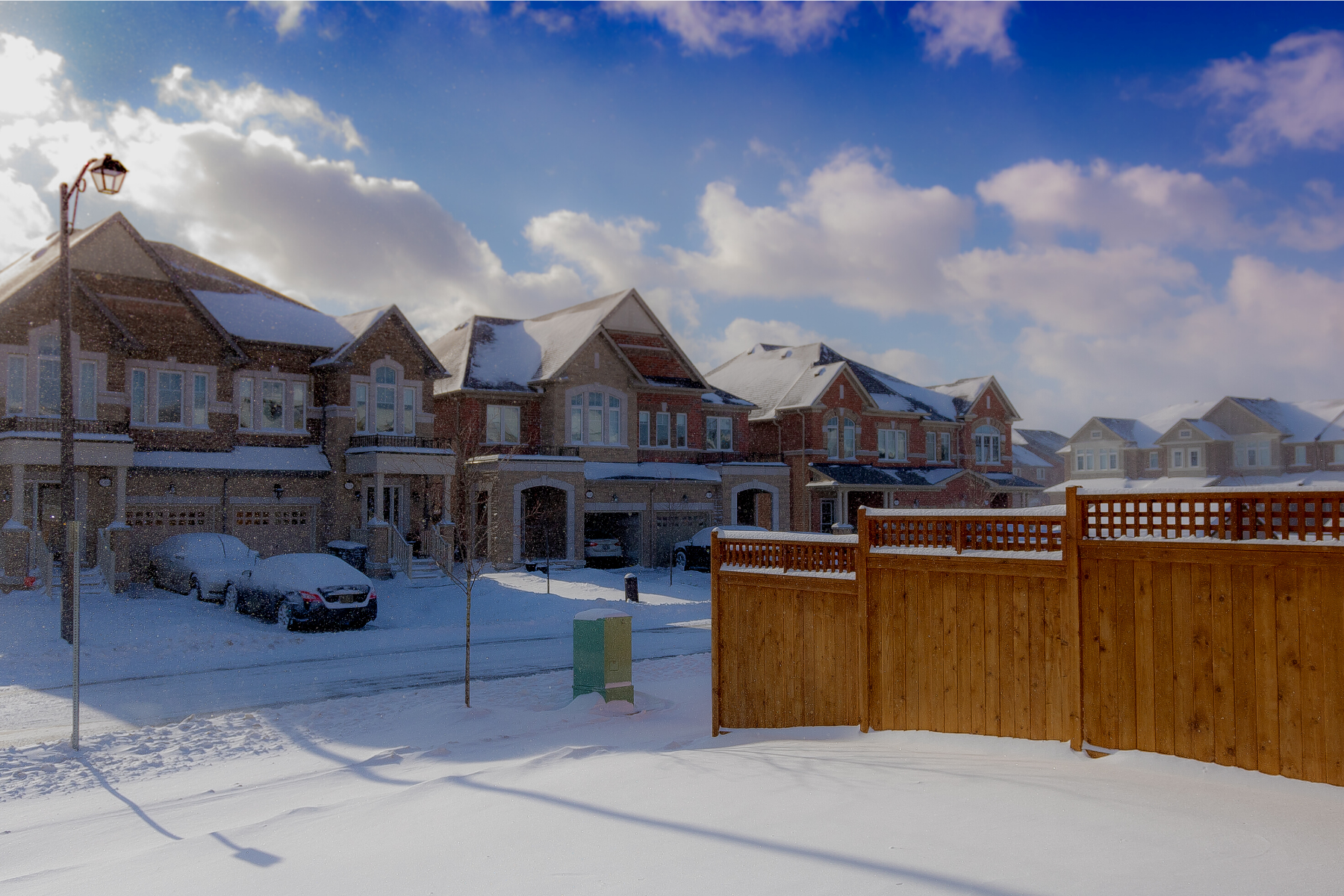 Snowy street with several houses and a wooden fence on a sunny, partly cloudy day
